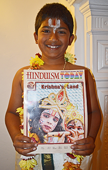 Young boy holding copy of Hinduism Today